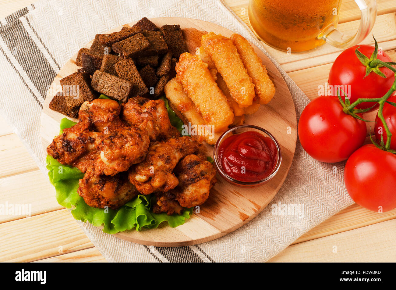 Fried wings, dried bread and cheese sticks with mug beer, served with sauces on a wooden background Stock Photo