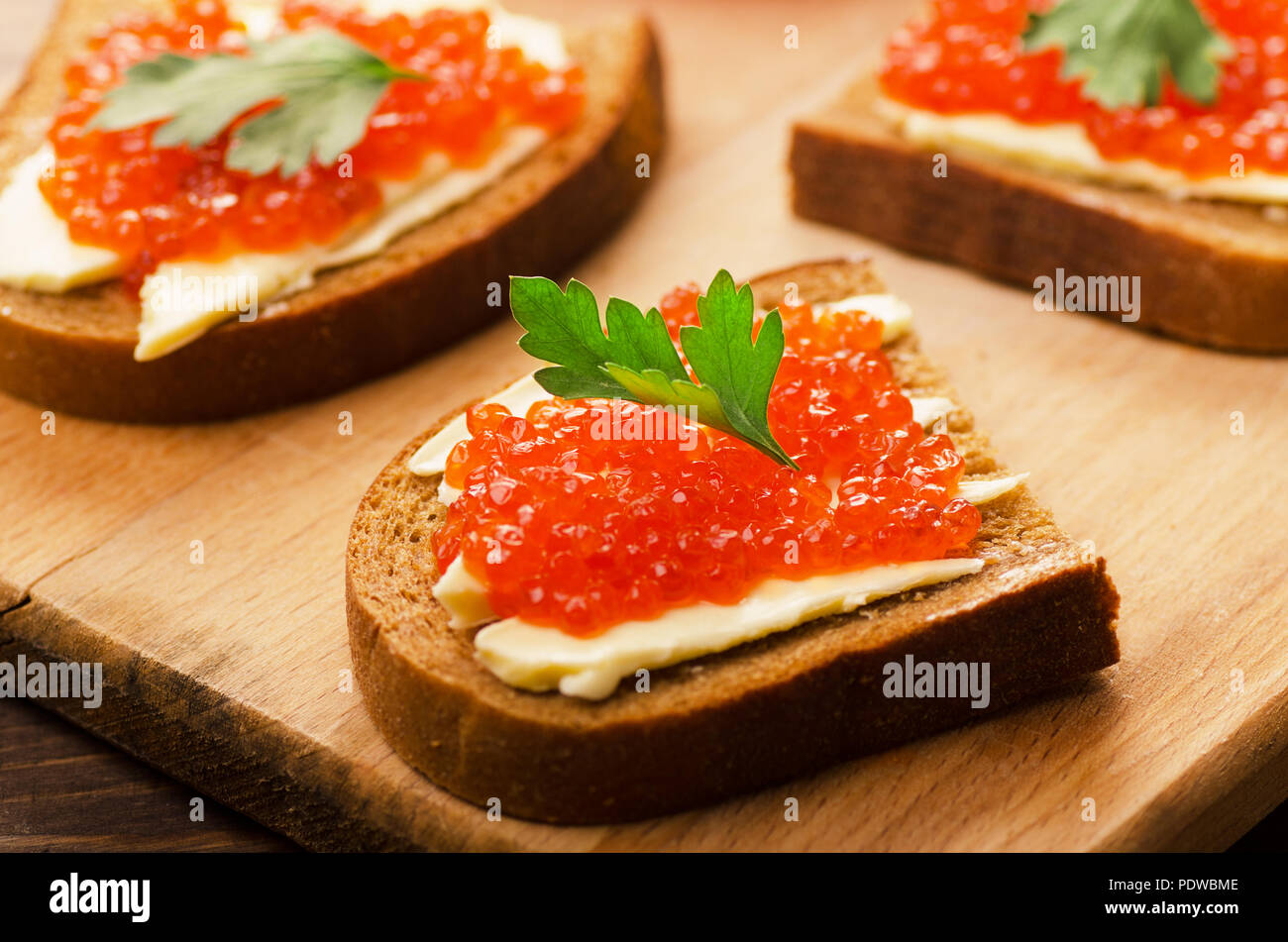 Sandwiches with red caviar on cutting board - Stock Image