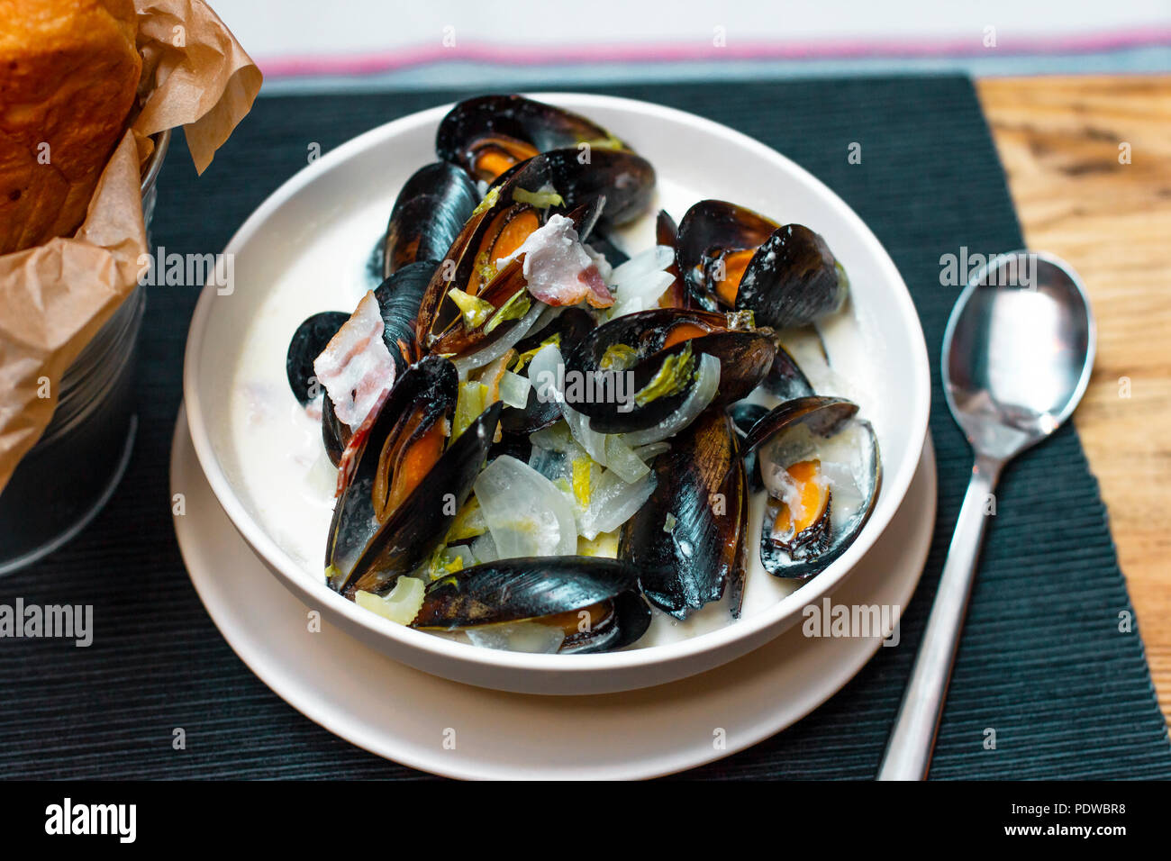 Mussels with onions and bacon in cream sauce in deep plate - Stock Image