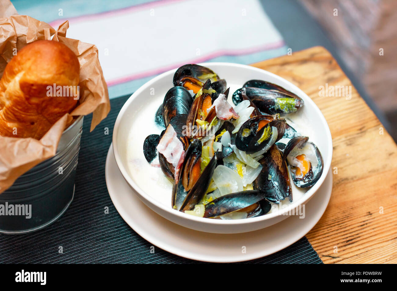 Mussels with onions and bacon in cream sauce in deep plate with bread on the table - Stock Image