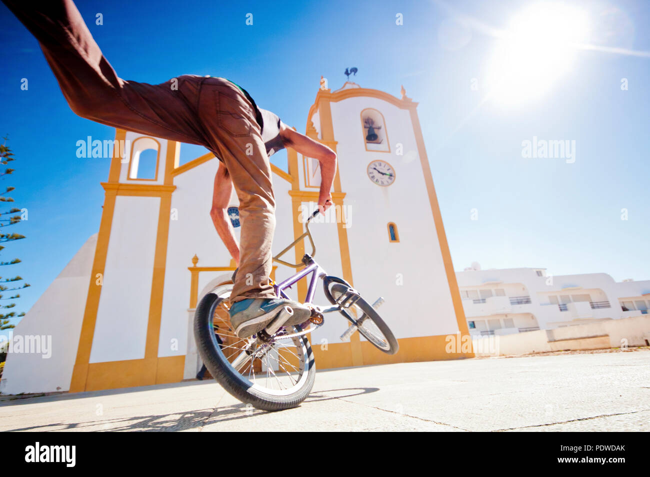 young man have fun doing tricks with freestlye bike in a sware in front of a church. contrast between classic and modern related lifestyle. sunny day  - Stock Image