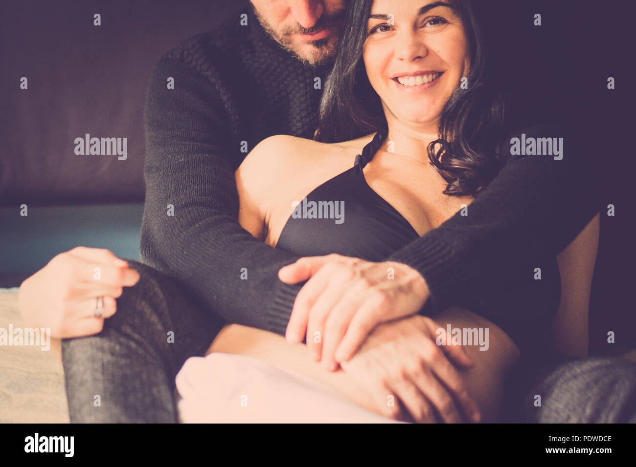couple in love at home lay down on the bed smile and look eachother with tenderness. caucasian people indoor activity. She pregnant for new family and - Stock Image