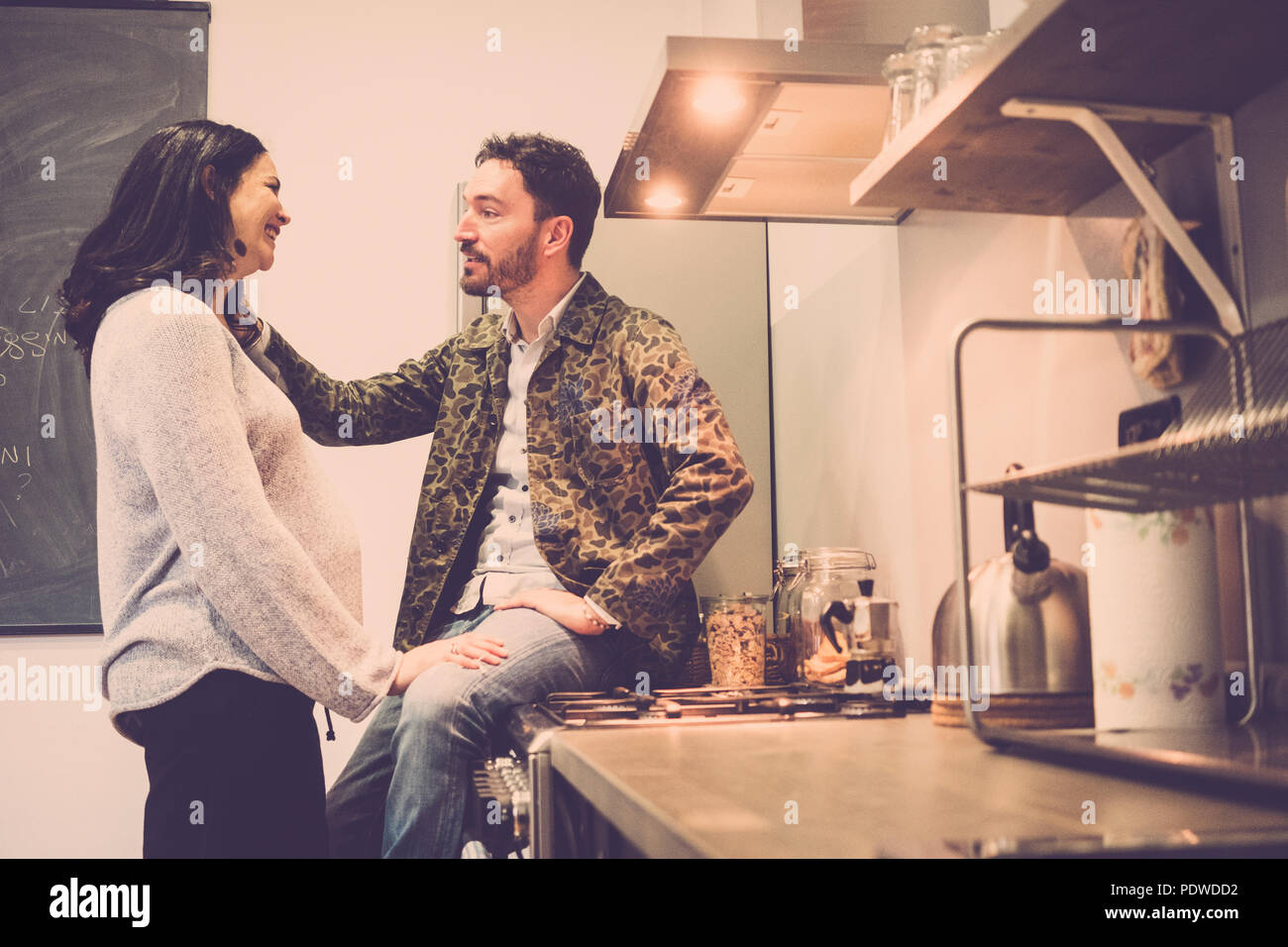 nice caucasian couple at home touching the belly and waiting for the new baby coming. pregnant concept for new mother and father. love workds, no bran - Stock Image