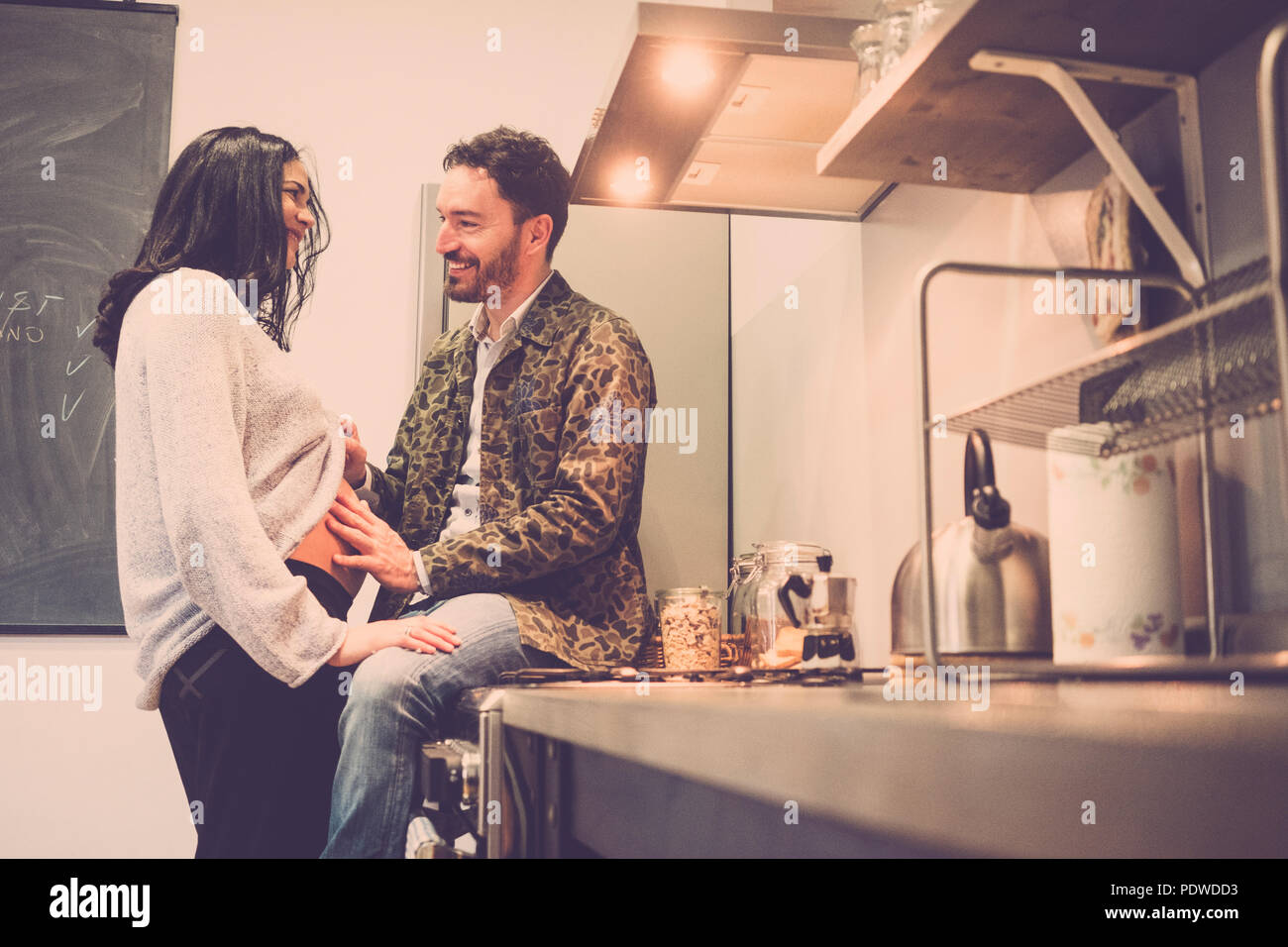 couple of man and woman caucasian happy people smile and have fun with the pregnant belly of the lady. smile and laugh waiting the new son . love work - Stock Image