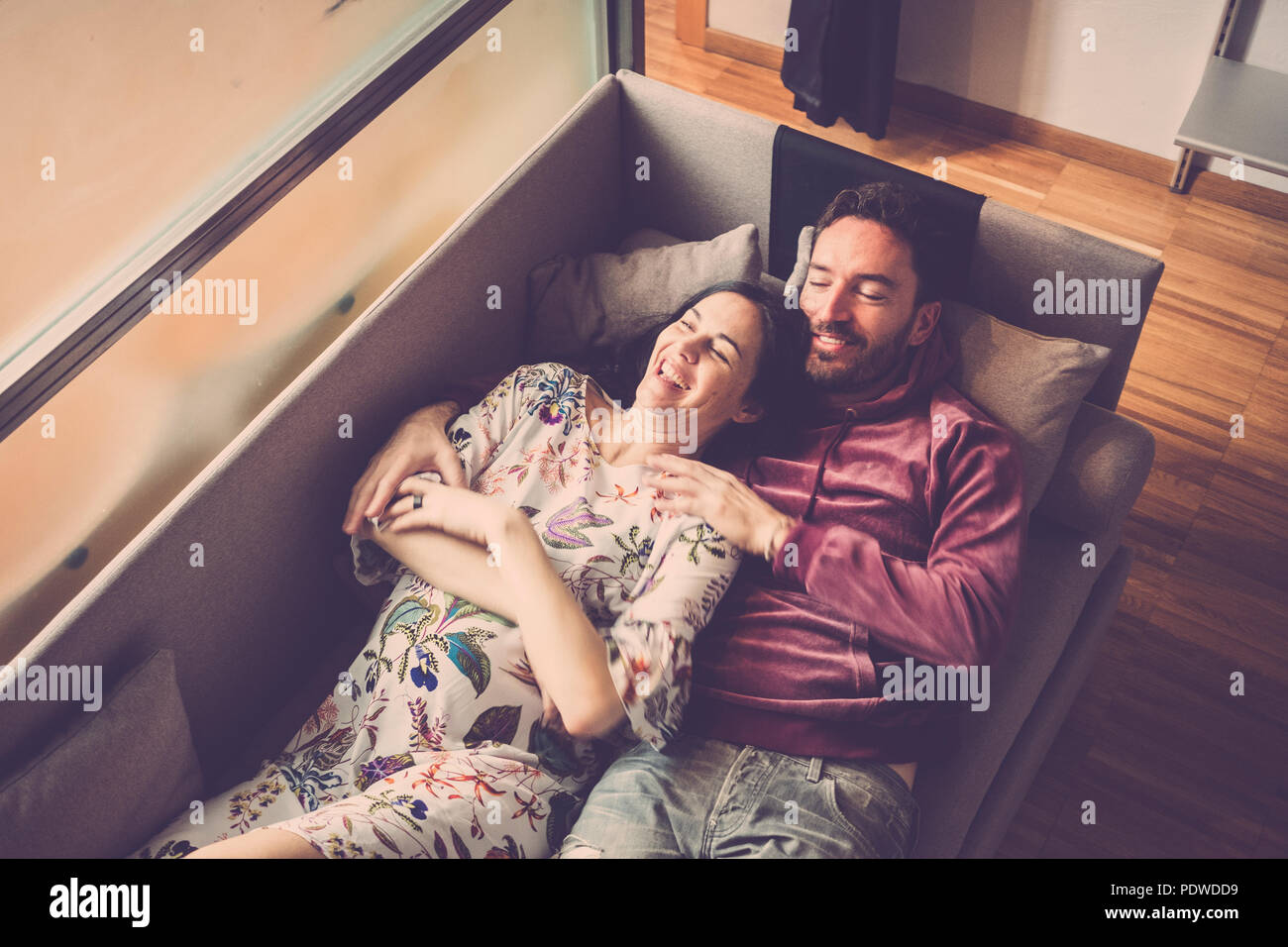 beautiful couple of models lay down on the sofa at home enjoying the lifestyle and relaxing. smile and cheerful people having leisure activity indoor - Stock Image