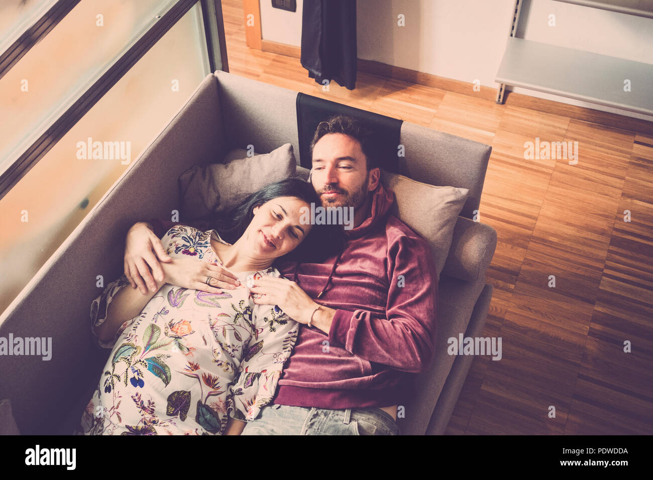 love and relationship concept for caucasian man and woman lay down on the sofa at home. tenderness and love for nice people - Stock Image