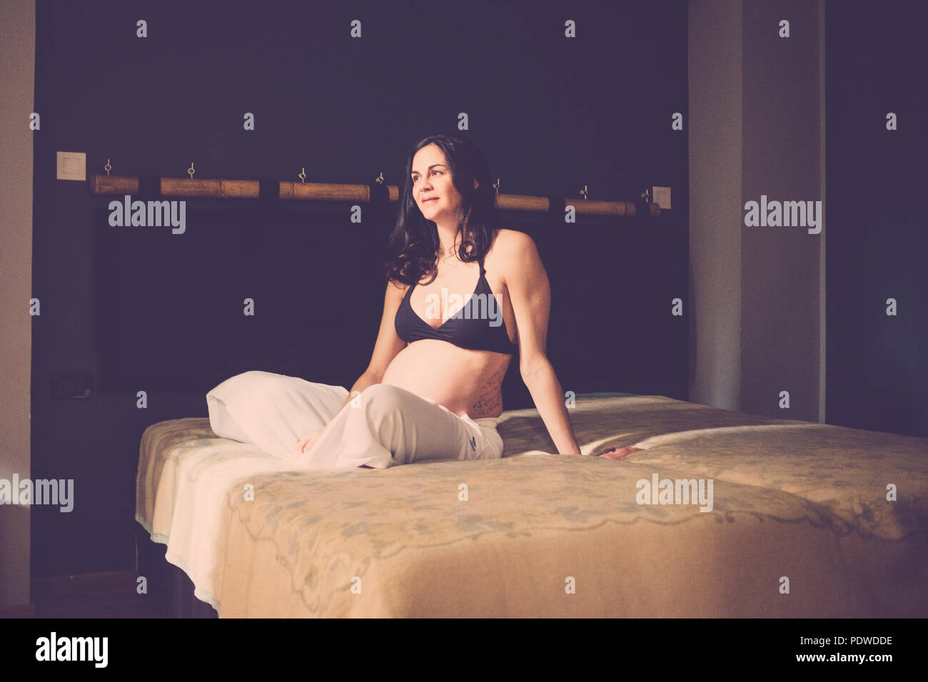 pregnant beautiful caucasian woman sitting on the floor and breathe to relax. new life concept at home. Alone in the bedroom Smile and happiness for n - Stock Image