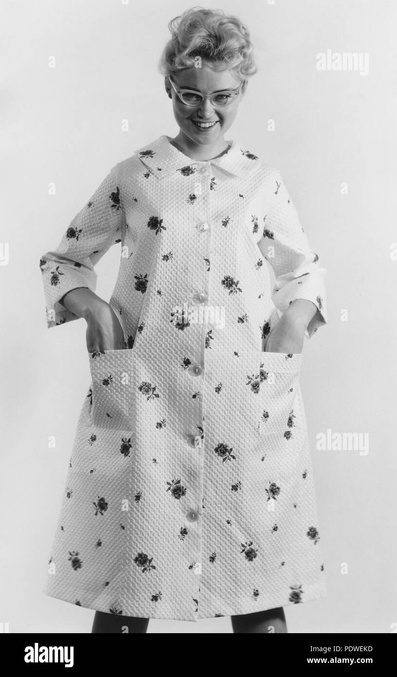 1950s glasses and fashion. A young smiling woman is dressed in a morning gown. 1950s - Stock Image