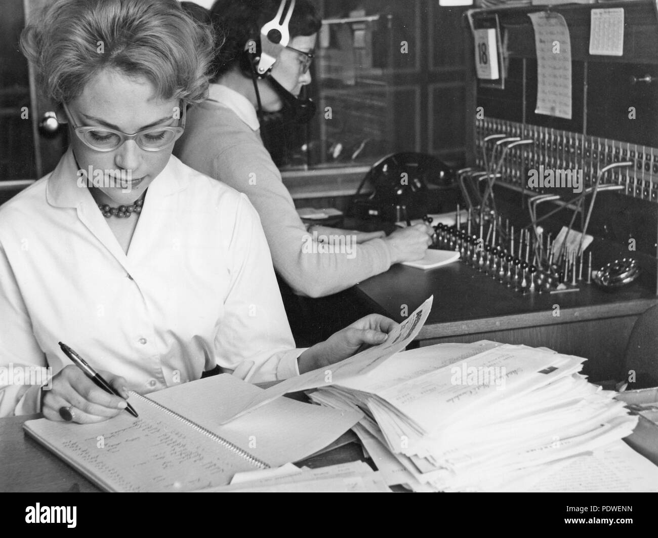 1950s office clerk and telephone switchboard operator. A young office worker is sitting at her desk handling documents. A telephone operator is sitting behind her taking incoming calls and connecting them further. 1958 - Stock Image