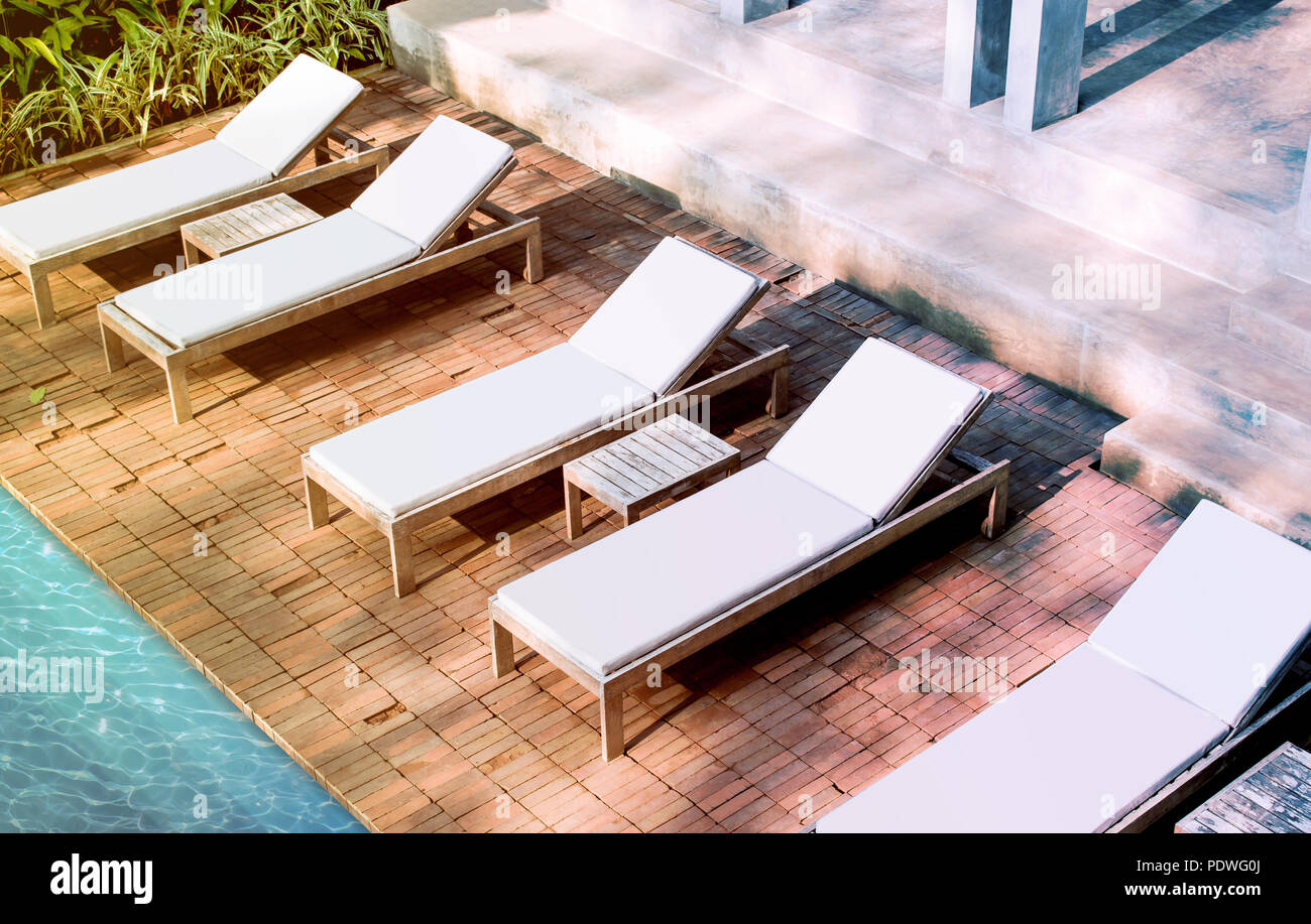 Blank white loungers mock up near swimming pool near luxury hotel. Lounge mockup for summer holidays. Sunbed for sunbathing in the inn template. - Stock Image