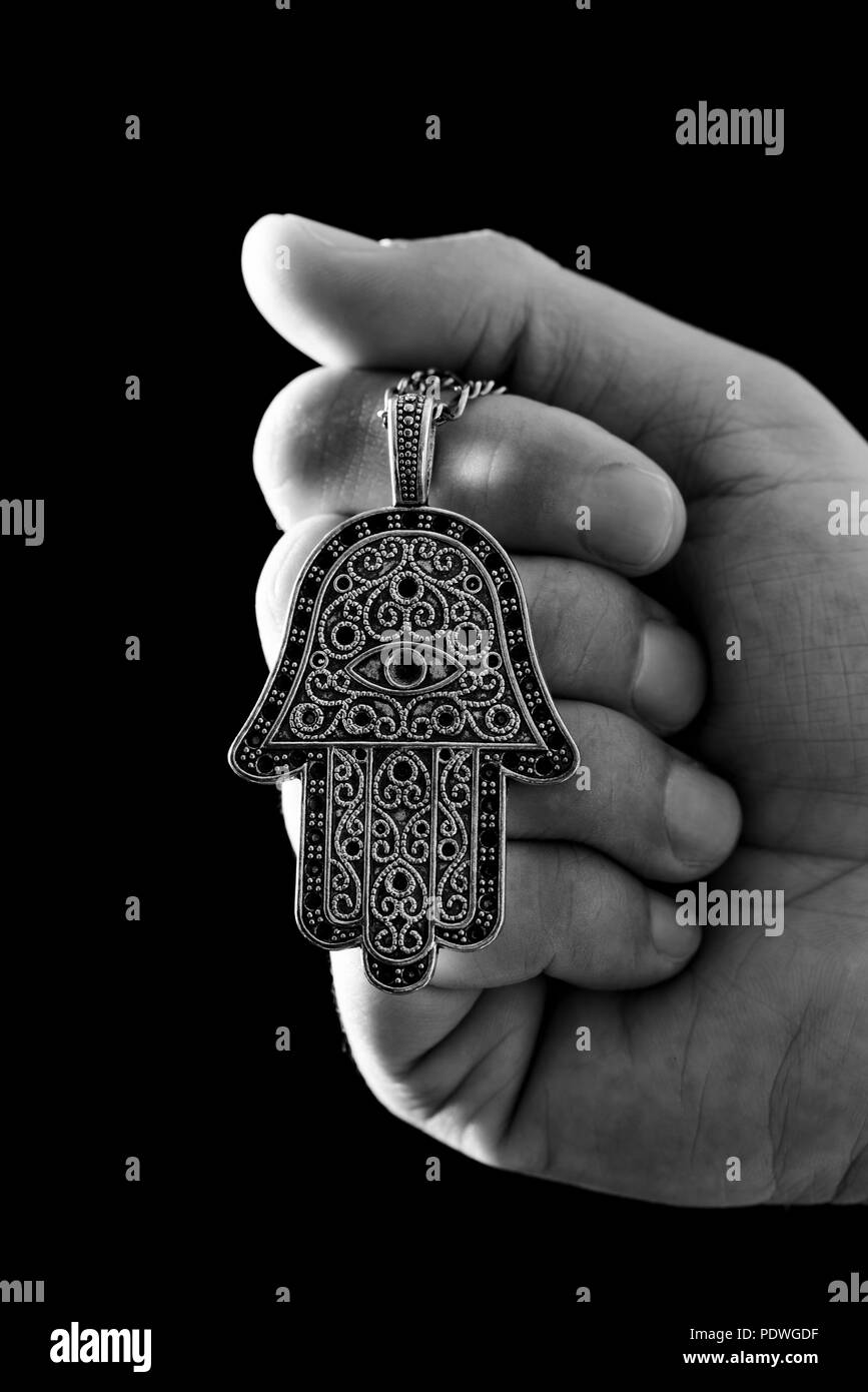 closeup the hand of a young man holding an old hamsa amulet, also known of the hand of fatima or the hand of mary, in black and white - Stock Image