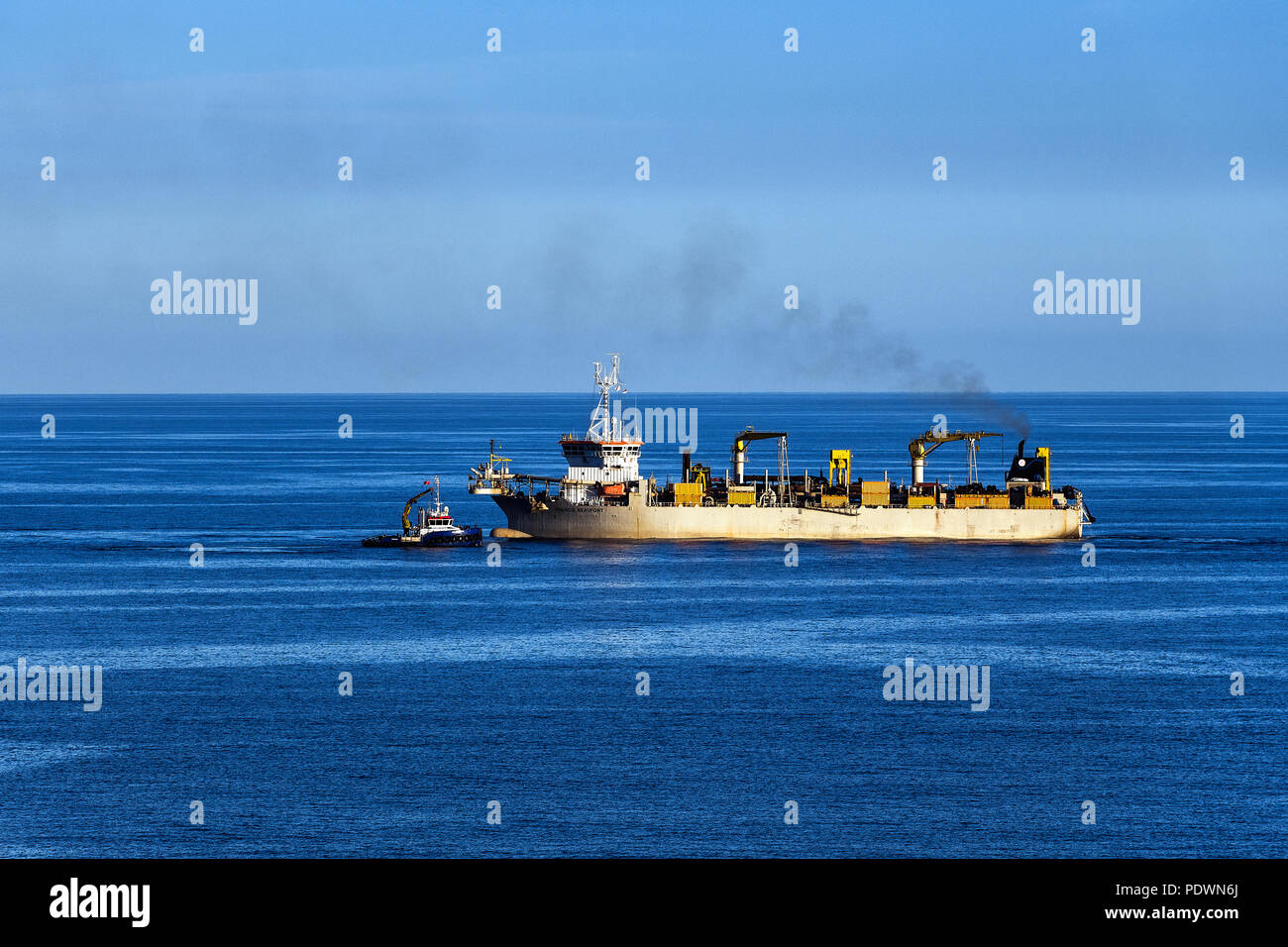 Trailing suction hopper dredger being assisted by a tug boat, Medeterranean Sea - Stock Image