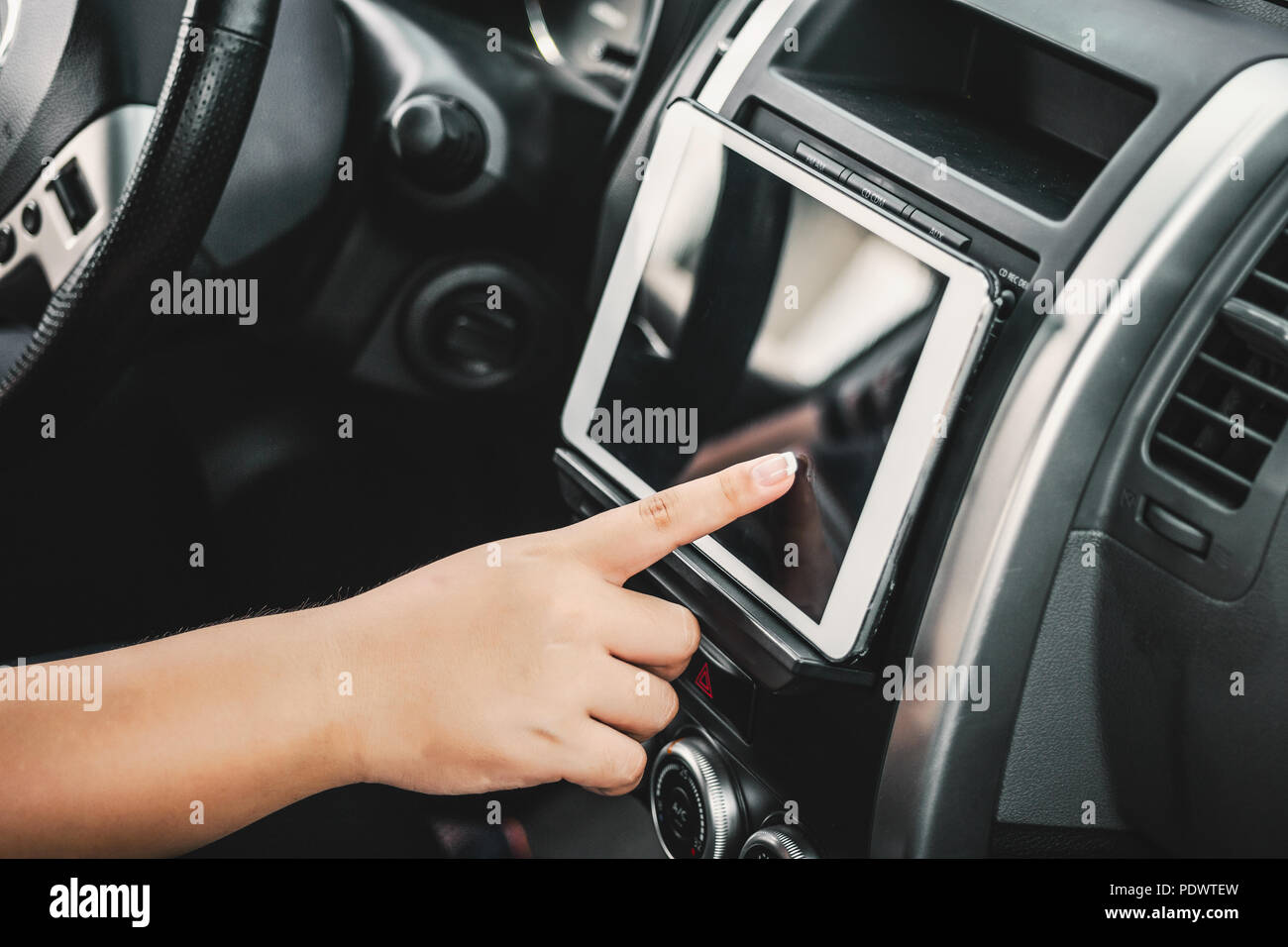 Man sitting in car and holding tablet with map gps