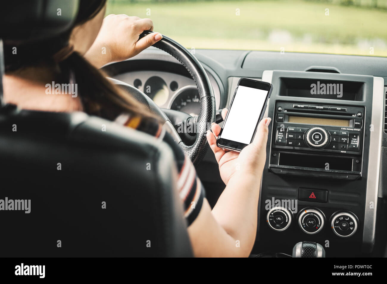 Young female driver using touch screen smartphone and gps navigation in a car. - Stock Image