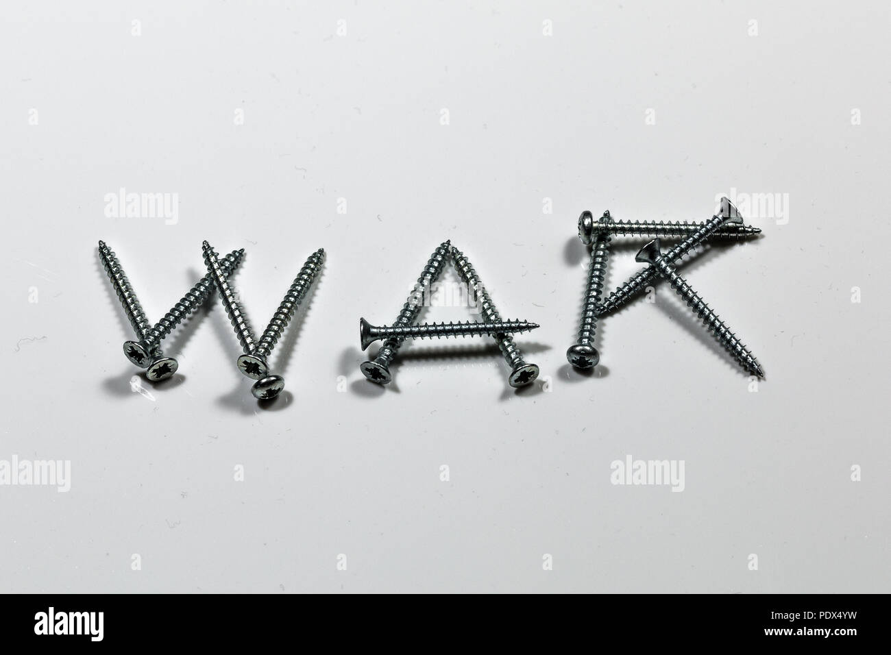 The word WAR written with screws on white background - Stock Image