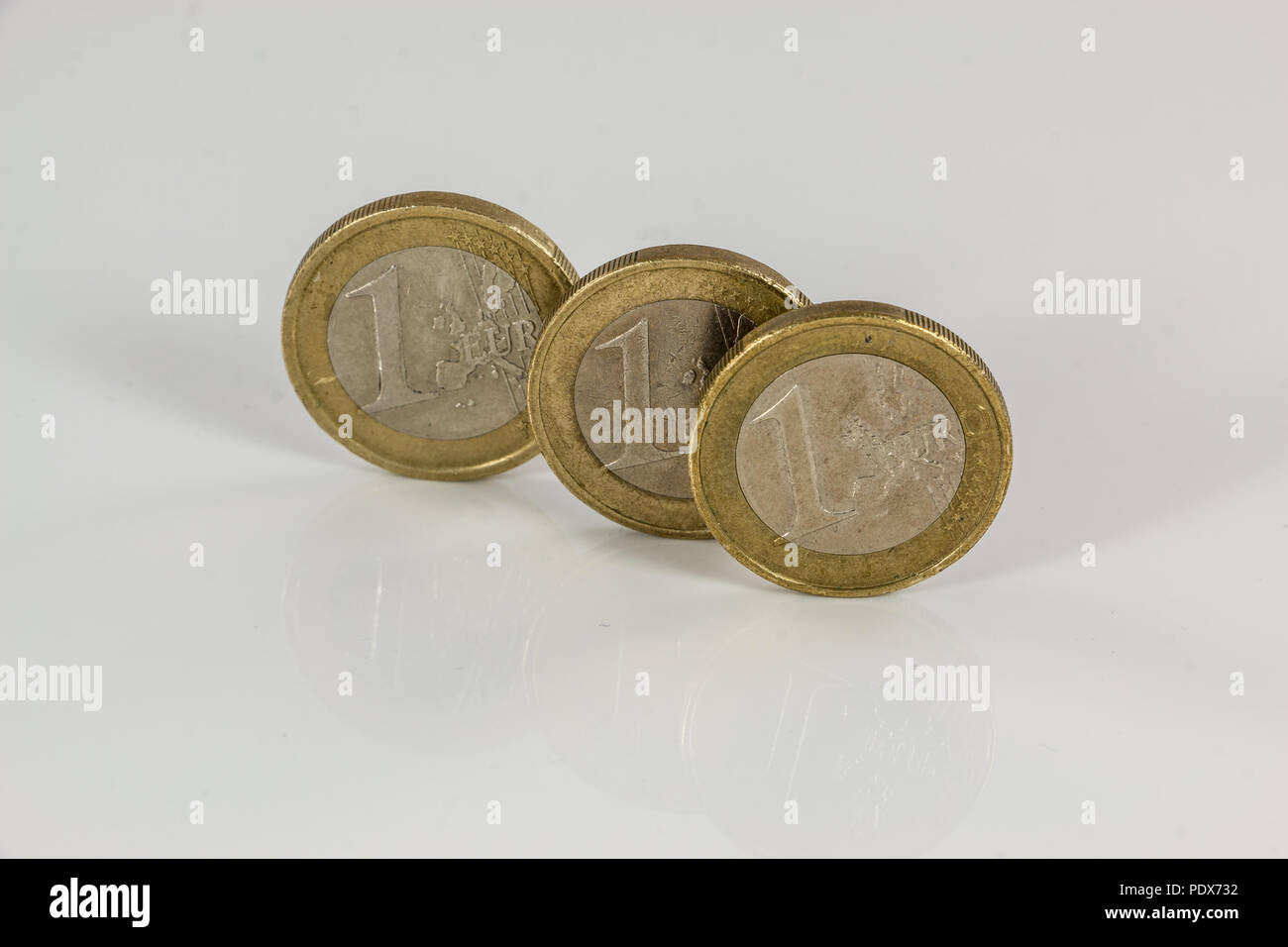 Euro coins on white background with reflections - Stock Image