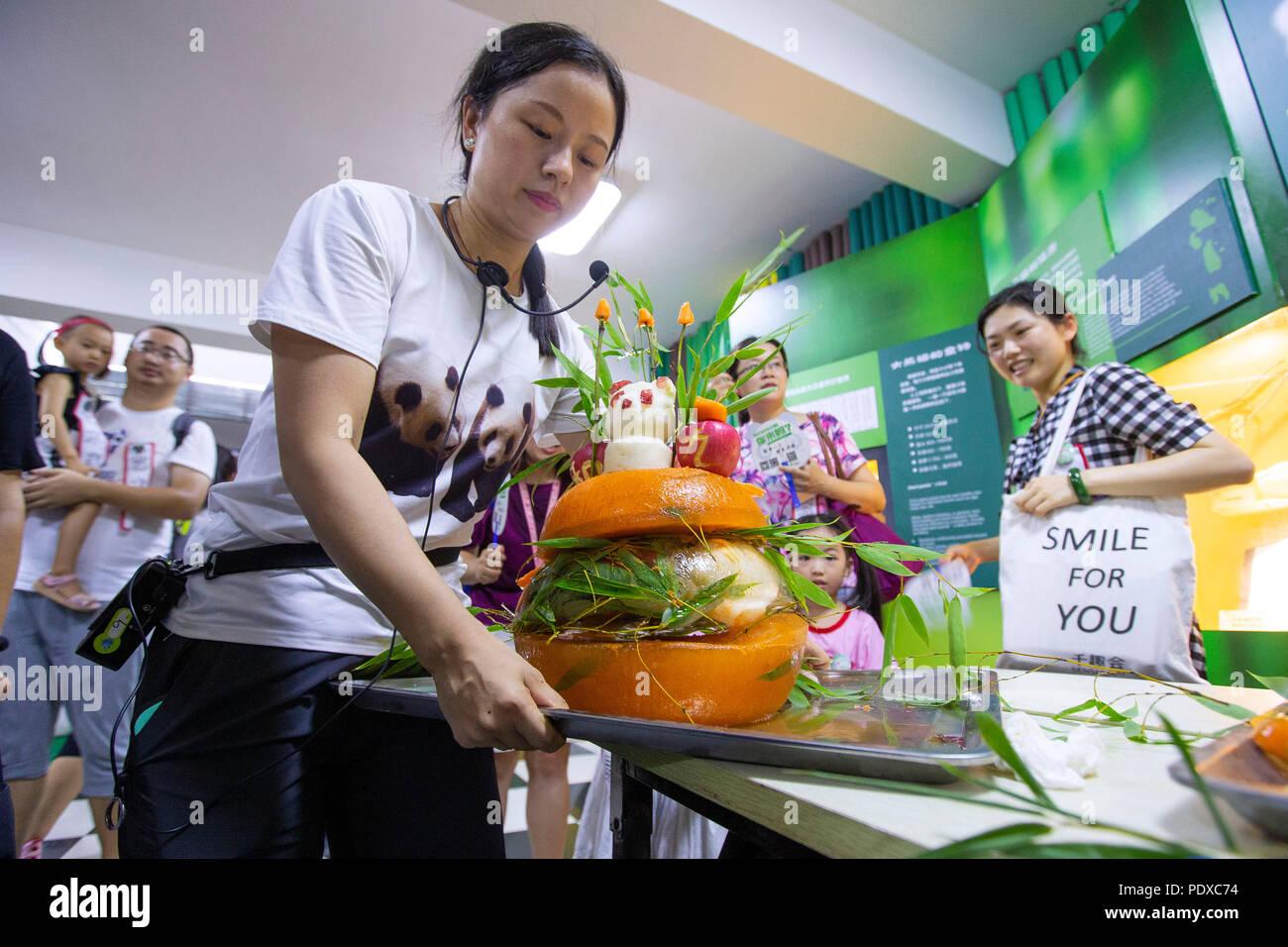 Nanjing, China's Jiangsu Province. 10th Aug, 2018. A staff worker shows a birthday cake prepared for the giant panda twins Hehe and Jiujiu at the Nanjing Hongshan Forest Zoo in Nanjing, capital of east China's Jiangsu Province, Aug. 10, 2018. Staff workers at the zoo celebrated the 3rd birthday anniversary for the female giant panda twins 'Hehe' and 'Jiujiu' on Friday. Credit: Su Yang/Xinhua/Alamy Live News - Stock Image