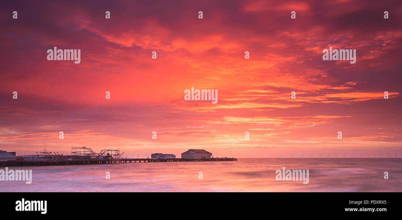 Sunrise behind the pier at Clacton-on-Sea, Essex, England, UK - Stock Image