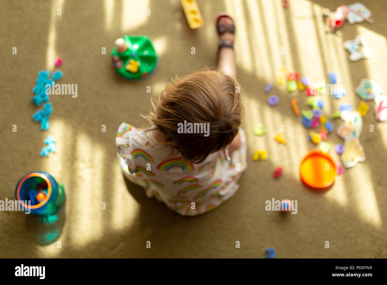 Young girl sat on floor surrounded by toys deep in thought, shot from above with narrow depth of field. - Stock Image