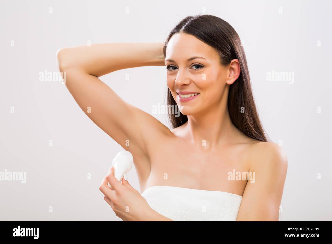 Beautiful woman using antiperspirant. - Stock Image