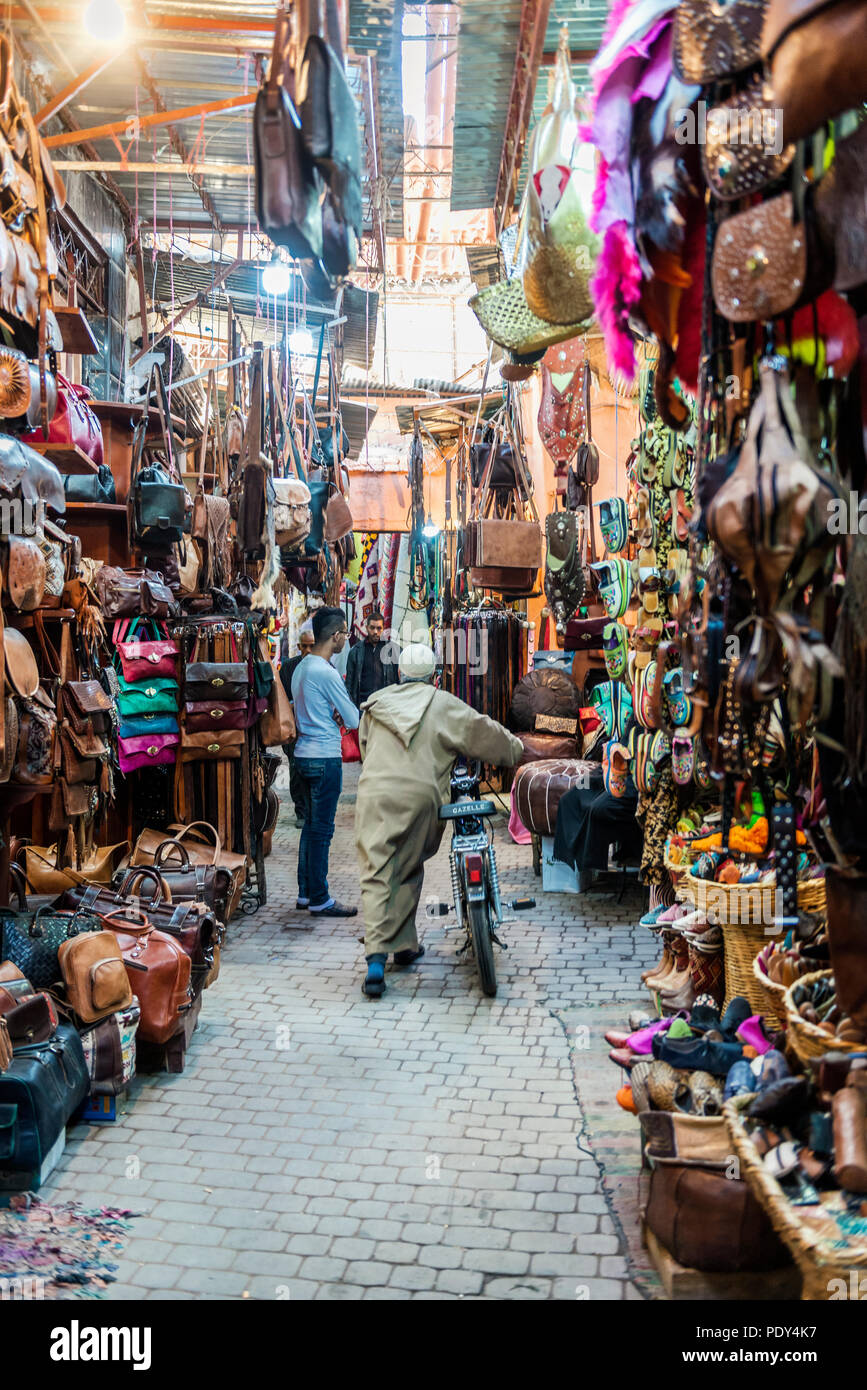 Local with a motorcycle, Narrow streets with leather goods in an Arabian market, Shouk, Fez Medina, Fes, Morocco - Stock Image