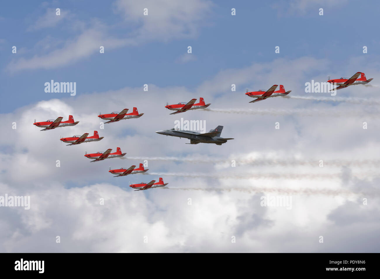 The Swiss Air Force Aerobatic Display Team in their PC-7 Turbotrainers fly in formation with a Swiss F/A-18C Hornet at the RIAT - Stock Image