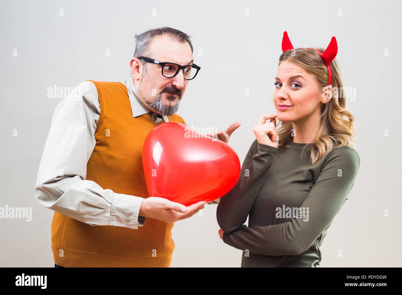 Nerdy man is uncertain in his girlfriend love. Stock Photo