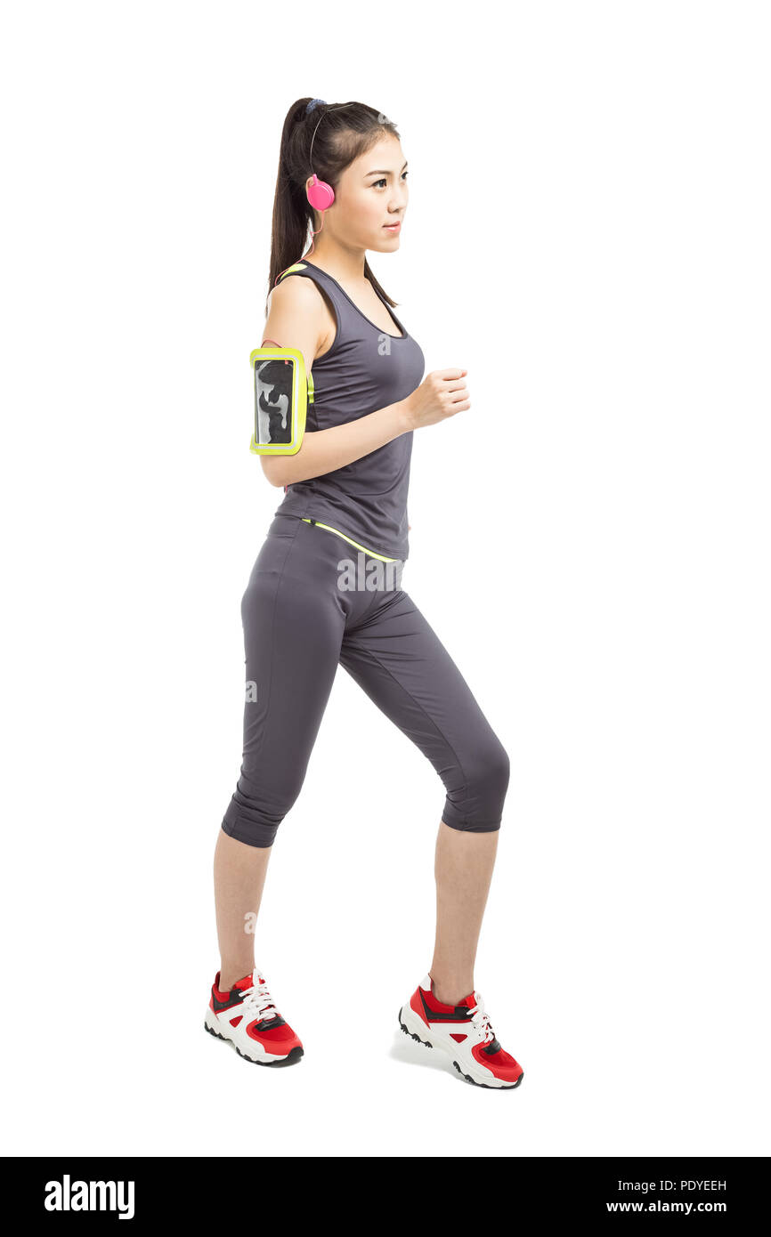 Young attractive female runner with armband running on sunset in park with earphones listening to music during training. Copy space - Stock Image
