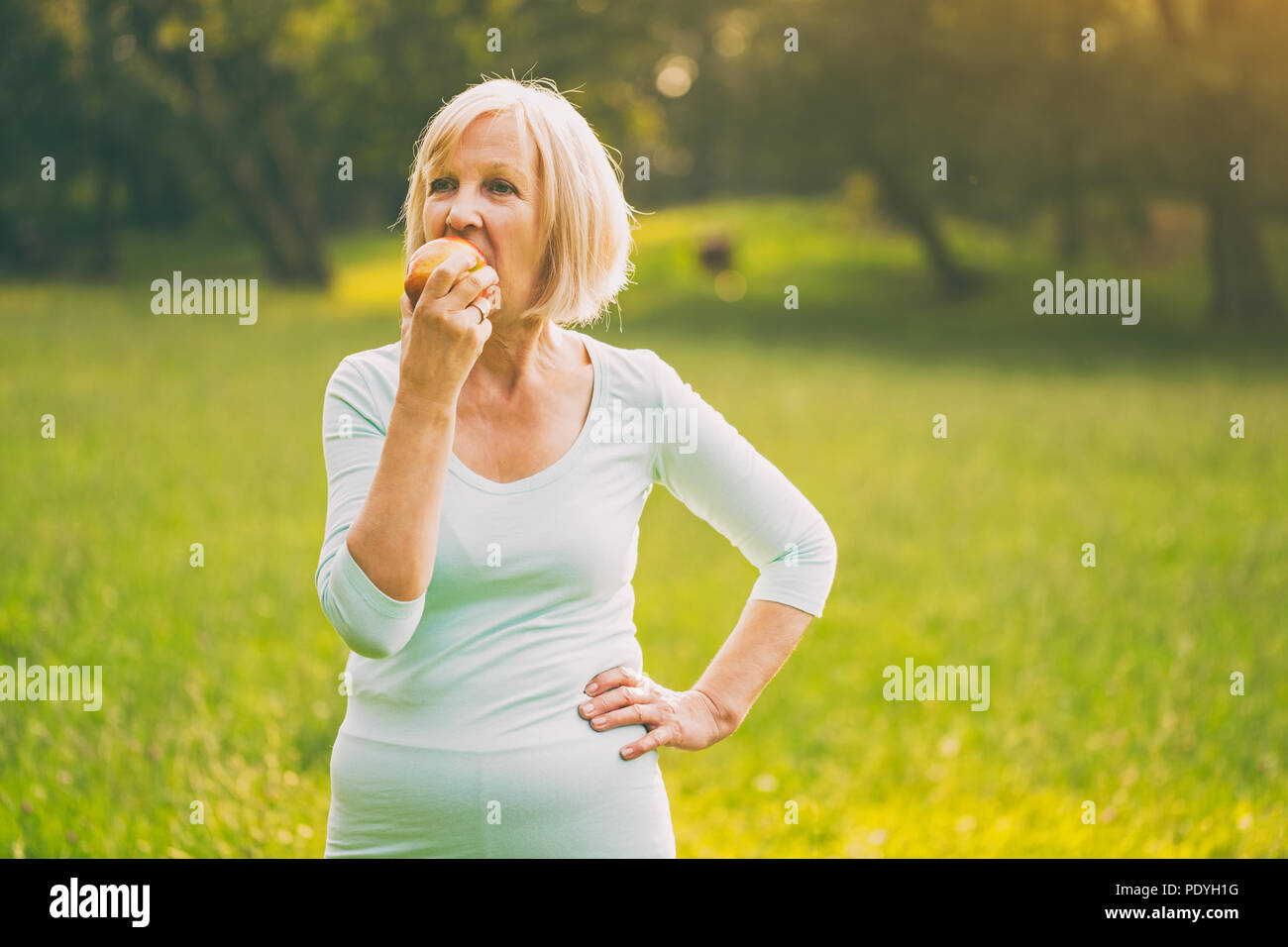Active senior woman eating apple after exercise.Image is intentionally toned. - Stock Image