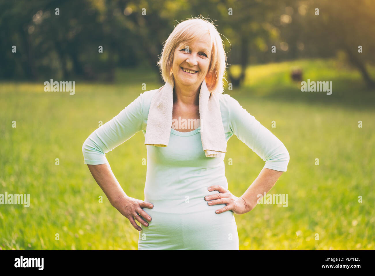 Portrait of sporty senior woman standing in the nature.Image is intentionally toned. - Stock Image
