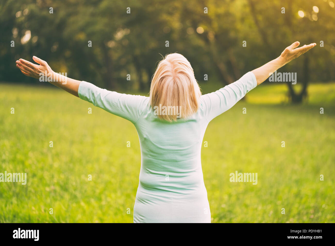 Senior woman enjoys with her arms outstretched in the nature.Image is intentionally toned. - Stock Image