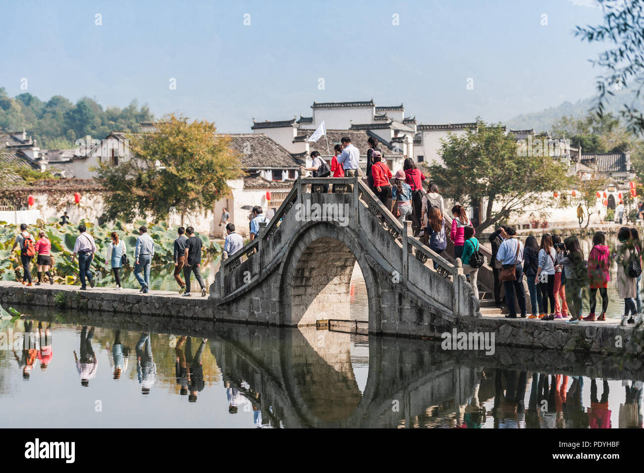 Tourists heading across the bridge to visit Hongcun Village, China. White buildings with ornate roofs. An ancient picturesque village. - Stock Image
