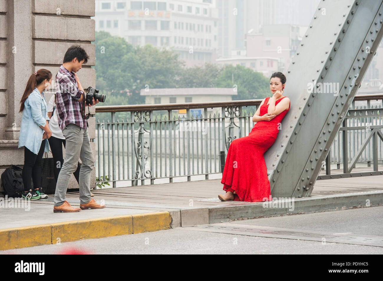 Shanghai, China - October 20, 2014. Photographer and a female fashion model during a photo shoot on a bridge over the Huangpu River in Shanghai. Stock Photo