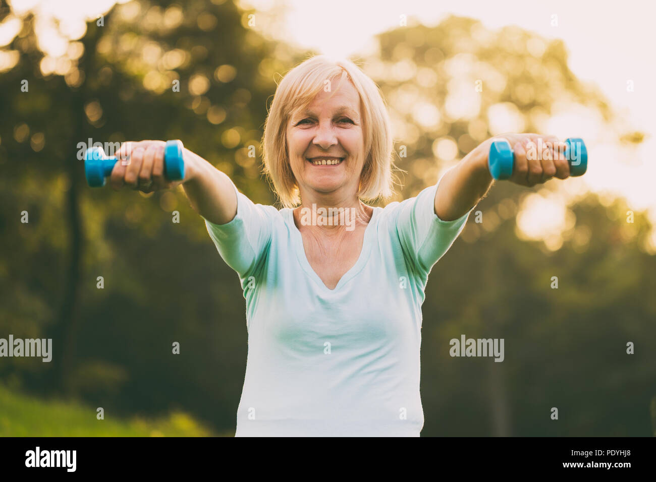 Sporty senior woman exercising with weights outdoor.Image is intentionally toned. - Stock Image