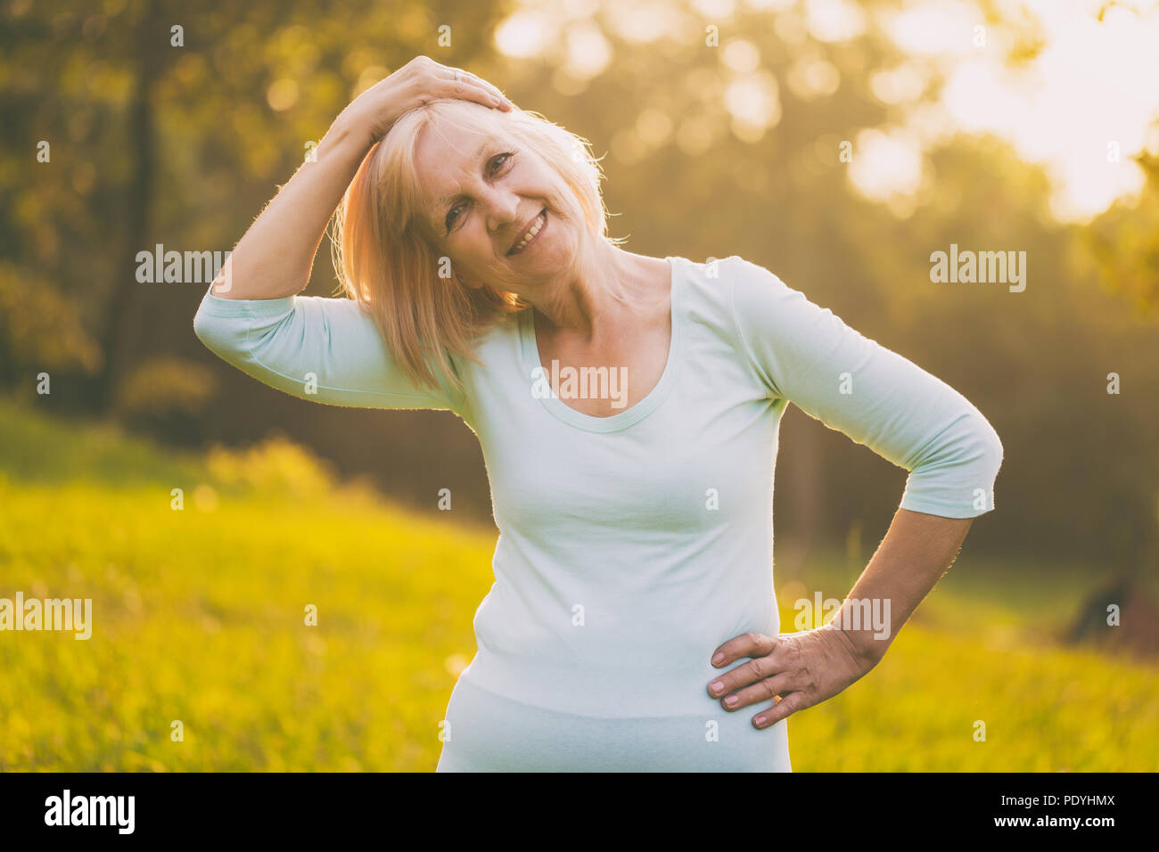 Sporty senior woman exercising outdoor.Image is intentionally toned. - Stock Image