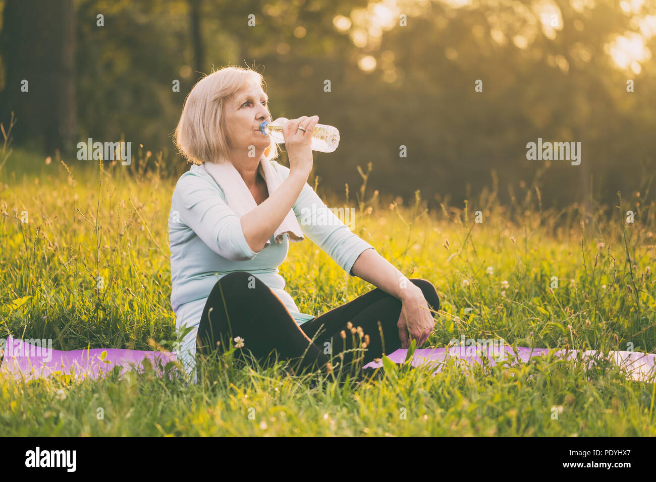Active senior woman drinking water during exercise.Image is intentionally toned. - Stock Image