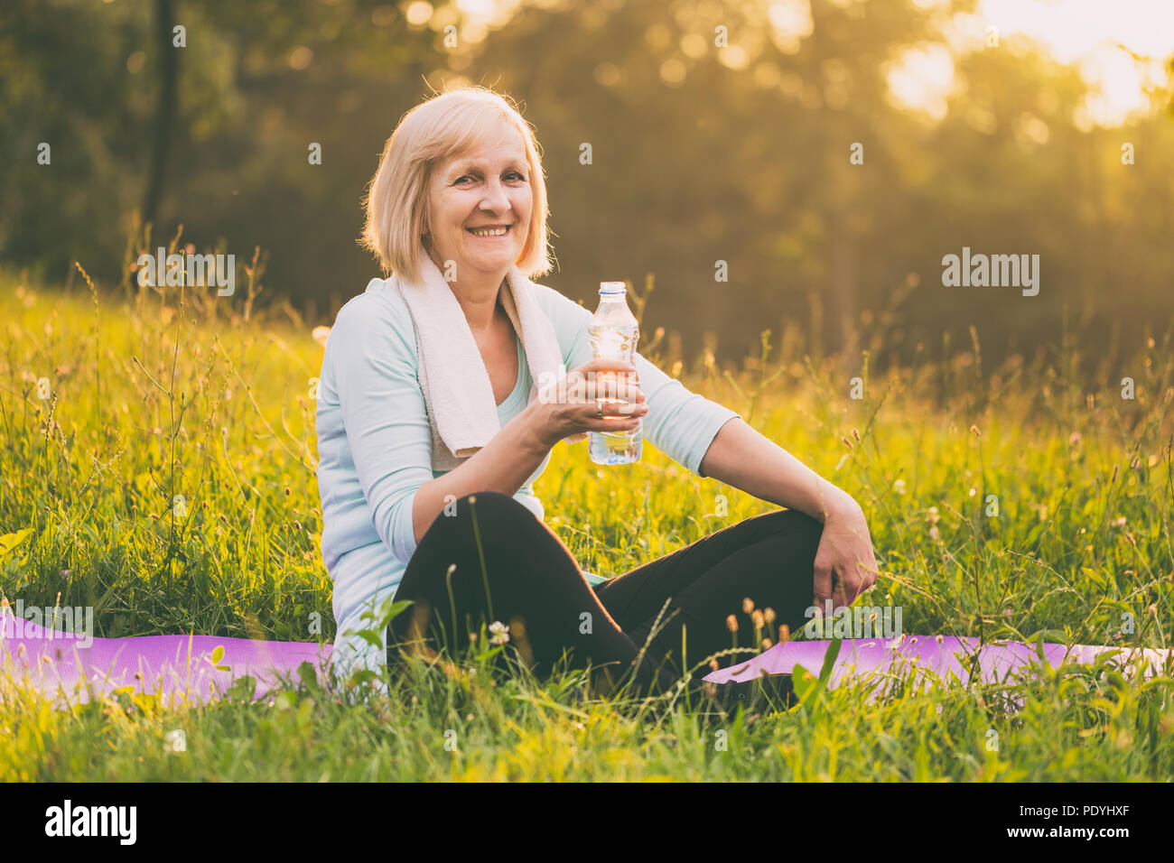 Portrait of active senior woman drinking water during exercise.Image is intentionally toned. Stock Photo