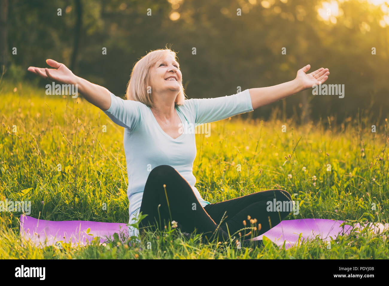 Senior woman enjoys sitting on the exercise mat with her arms outstretched in the nature.Image is intentionally toned. - Stock Image