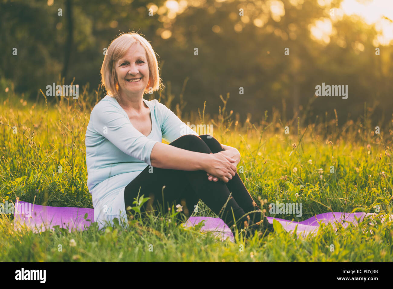 Portrait of sporty senior woman sitting on mat in the nature.Image is intentionally toned. - Stock Image
