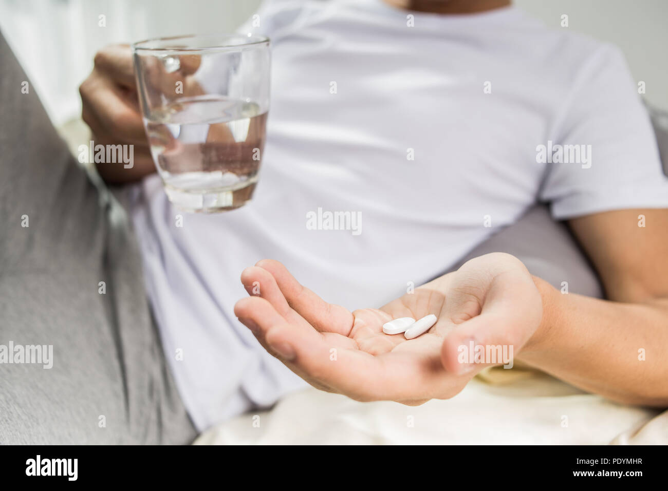Close up of man holding glass of water and pill in bright living room - Stock Image