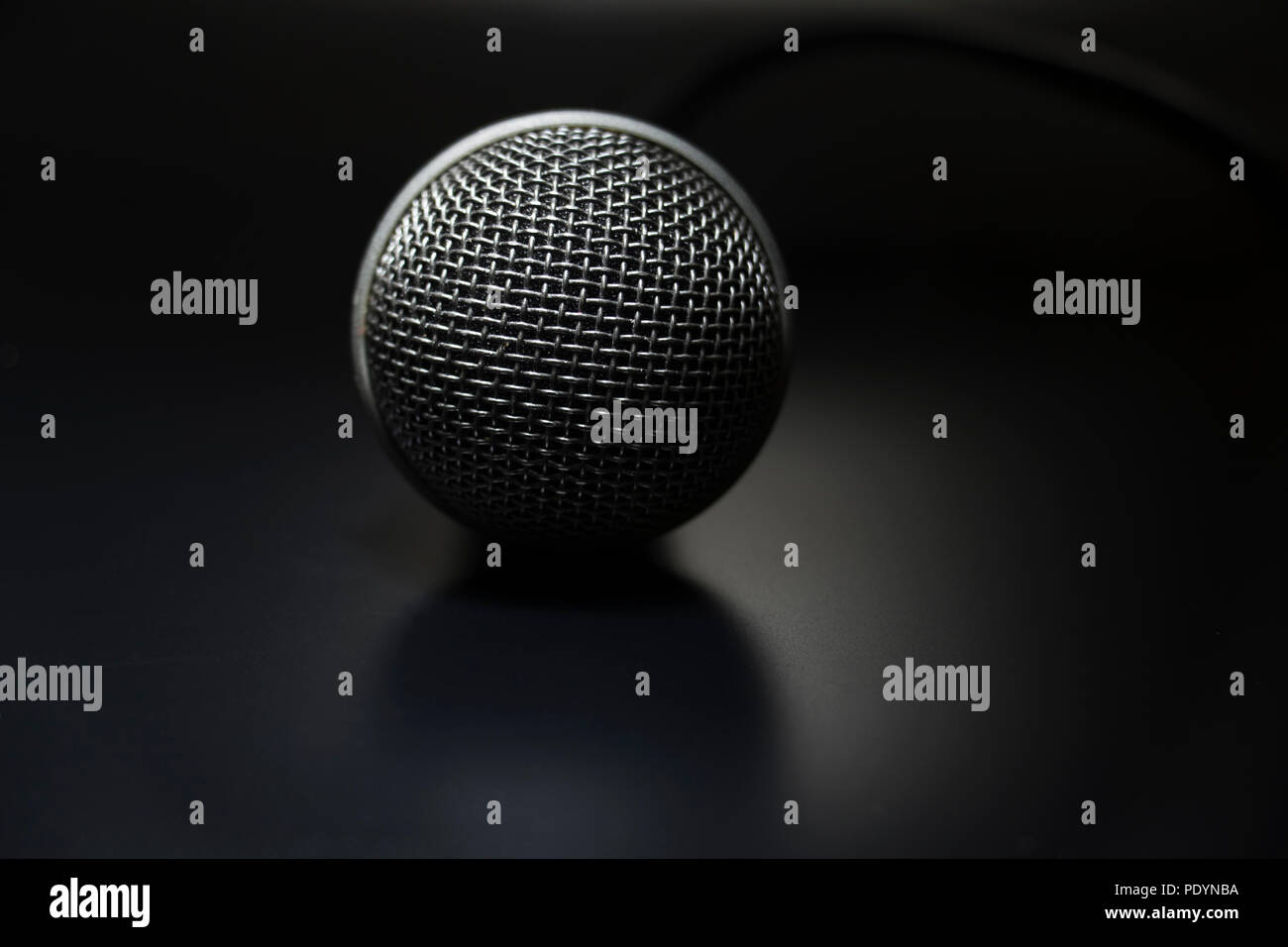 Close up of Microphone isolated on black background. Musical equipment used by a DJ and lead singer. - Stock Image