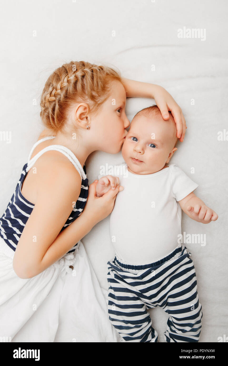 Lifestyle portrait of cute white Caucasian girl sister holding kissing little baby, lying on bed indoors. Older sibling with younger brother newborn.  Stock Photo