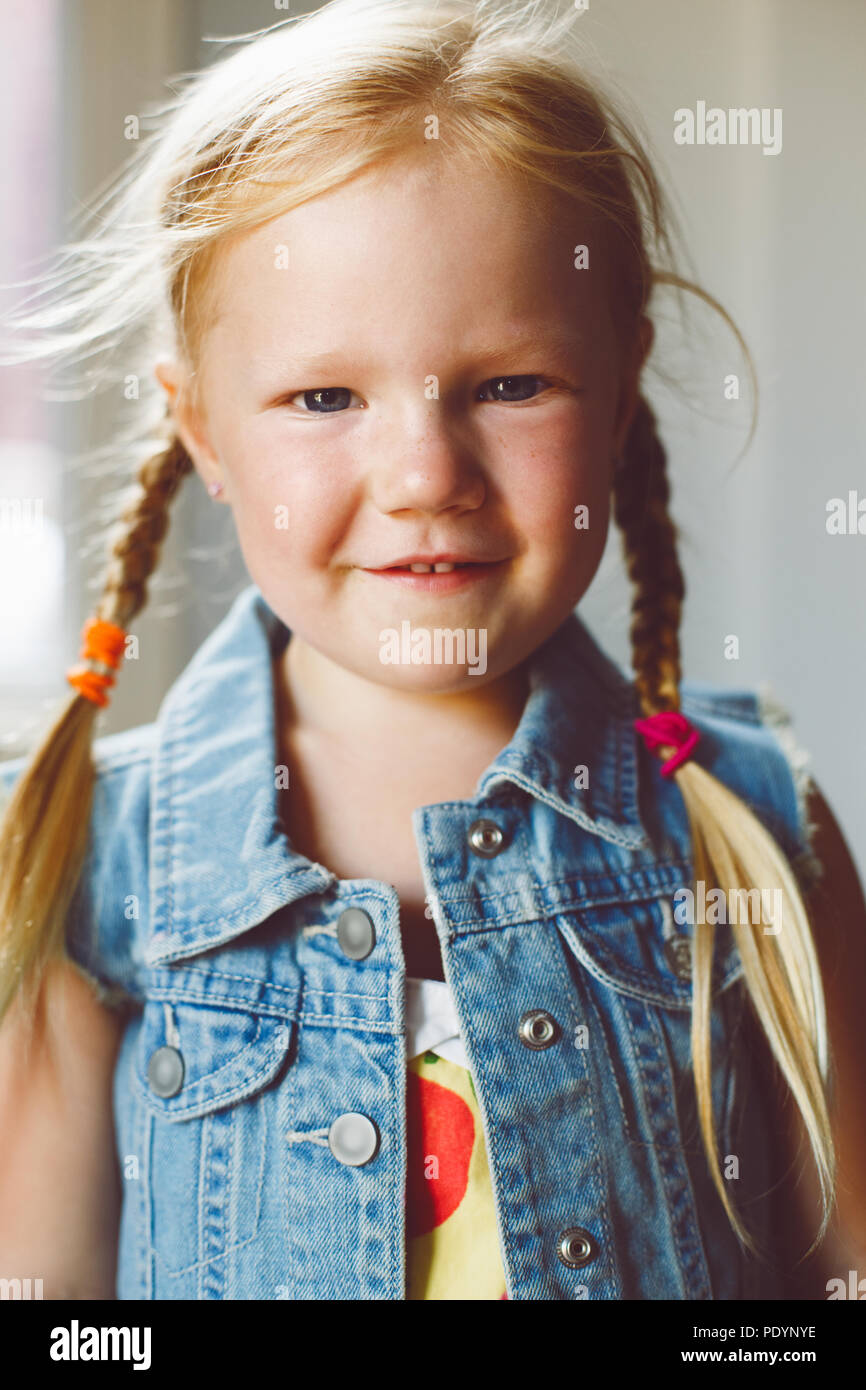 Closeup portrait of cute adorable white blonde Caucasian smiling girl looking in camera. Child girl with light fair hair with plaits, wearing country  - Stock Image