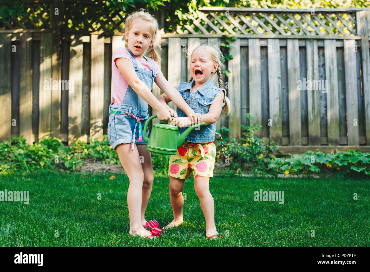 Portrait of  two little girls  sisters having fight on home backyard. Friends girls share watering pot can. Lifestyle family moment of siblings quarre - Stock Image