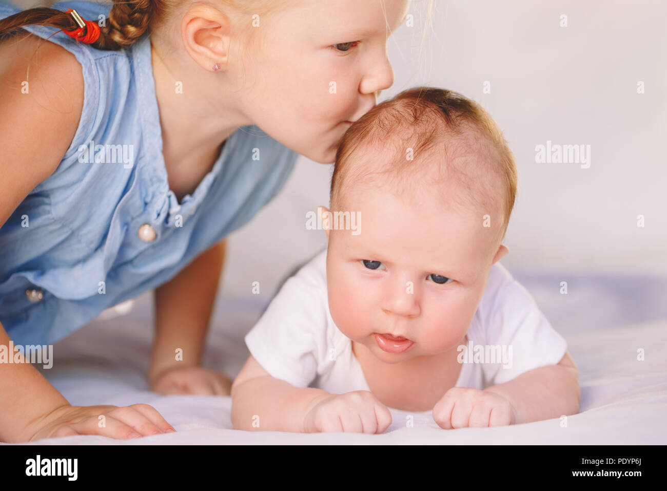 Lifestyle closeup portrait of cute white Caucasian girl sister kissing little baby, lying on bed indoors. Older sibling with younger brother newborn.  Stock Photo