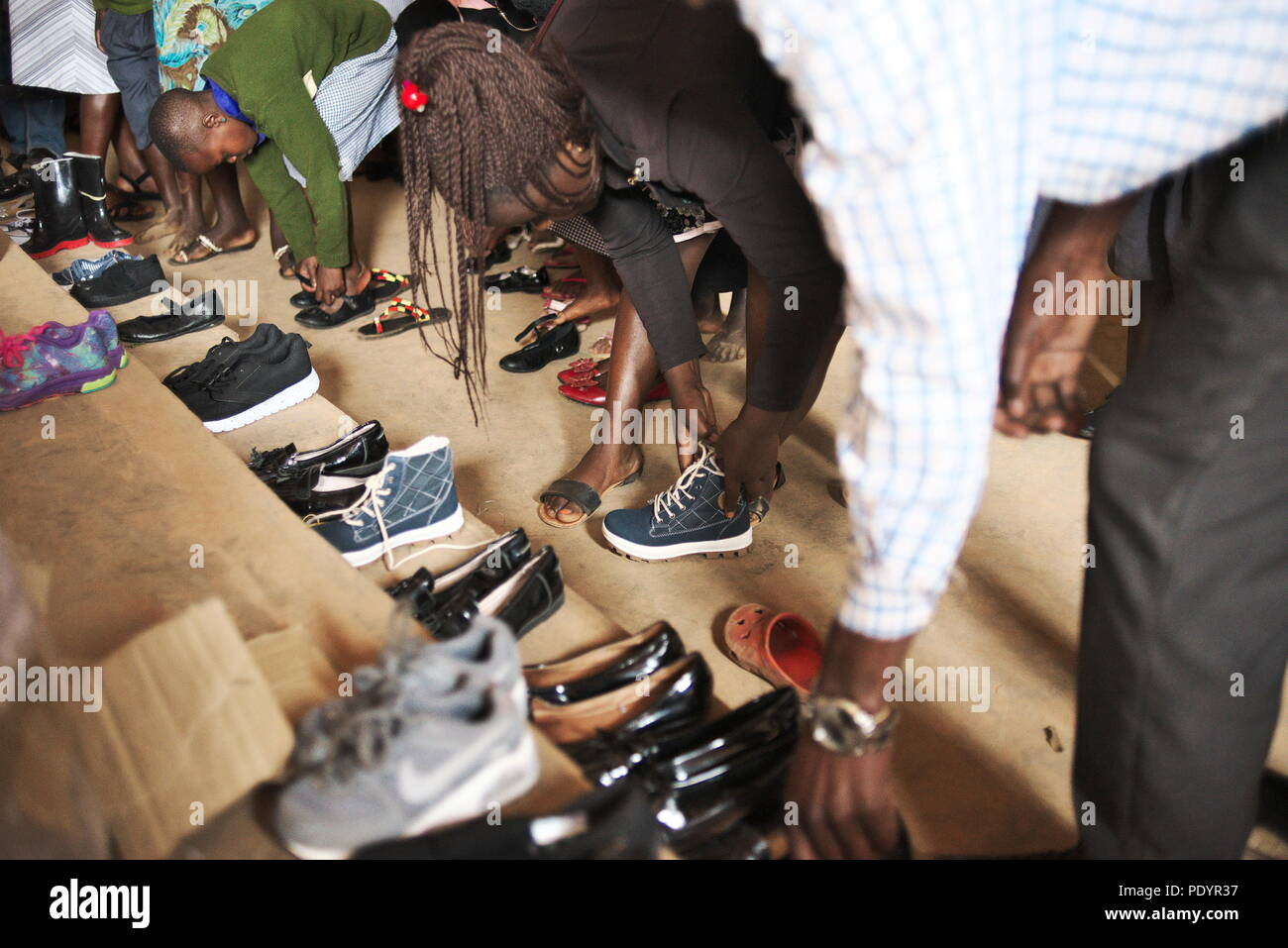 Young Ugandan/African schoolchildren try on used shoes given to the school as a gift from the UK - Stock Image