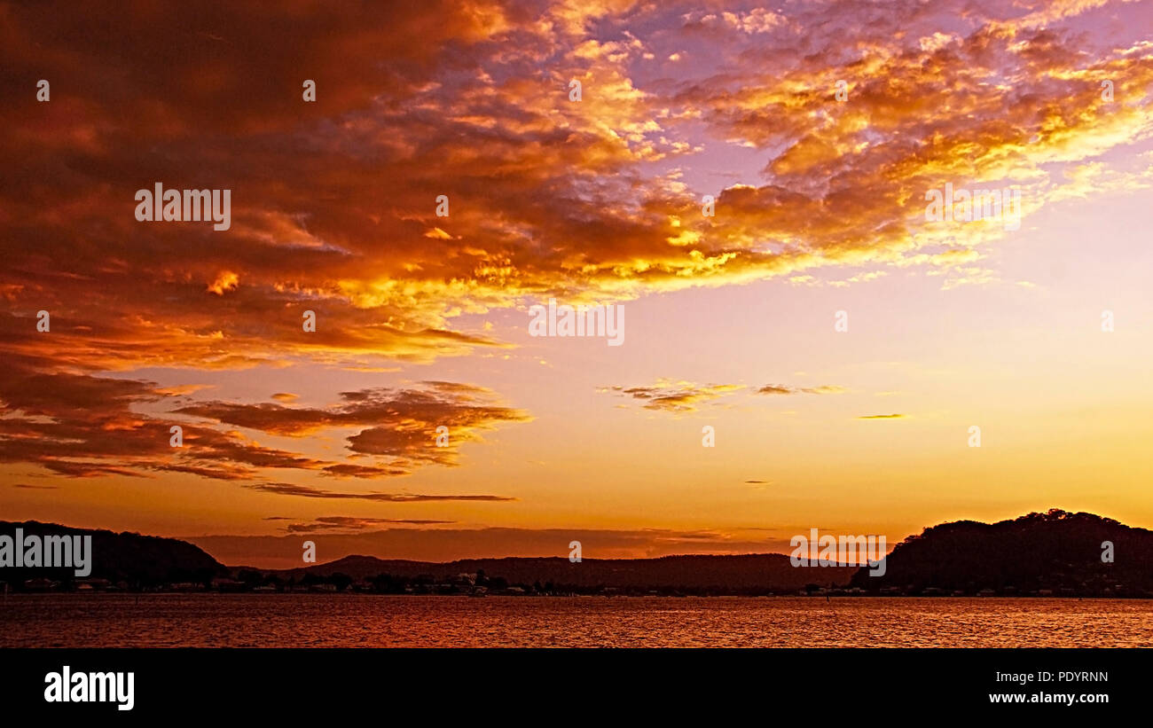 Delightful Orange skyscape sunset with predominantly Stratocumulus cloud, in a salmon orange, coloured sky. Seascape with ocean water reflections. - Stock Image