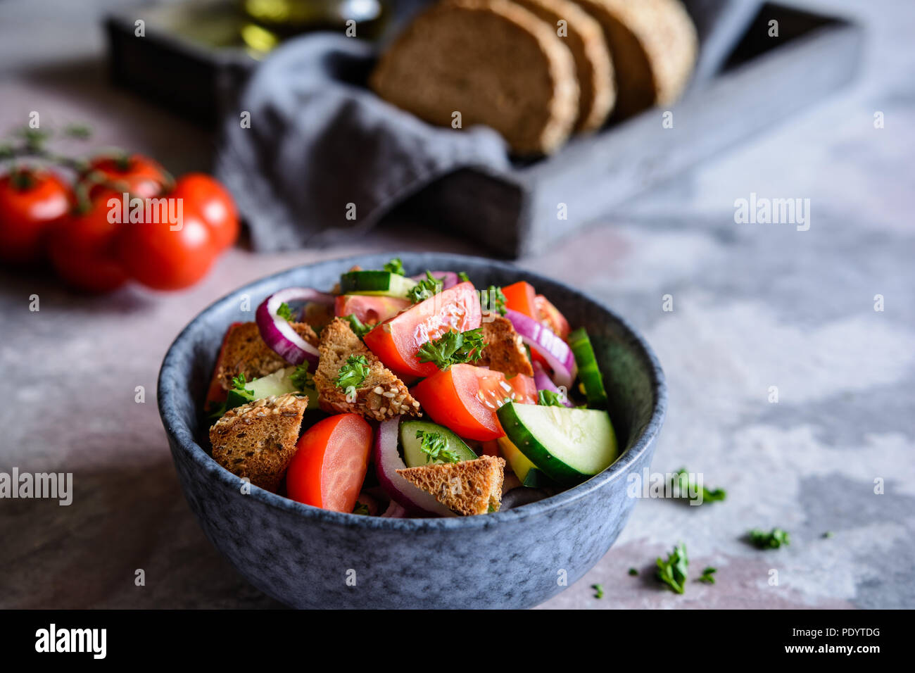 Panzanella - traditional Italian salad with cherry tomatoes, red onion, cucumber and bread croutons - Stock Image