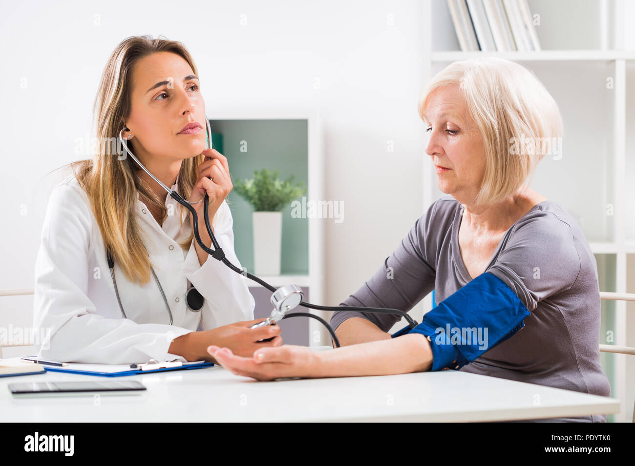Female doctor is measuring blood pressure to her senior patient in doctor's office. - Stock Image