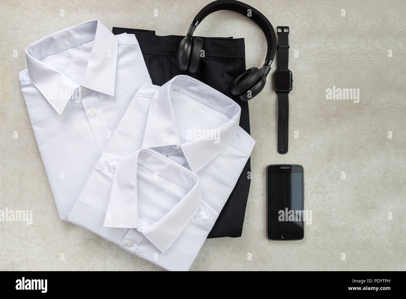 Back to school concept, school uniform such as white shirts and trousers, as well as electronic devices such as smart watch, mobile phone and headphon - Stock Image